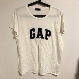 Oanvänd t-shirt från märket GAP. Trycket är i marinblått. Storlek XXL men mer som en L/XL. Köpt för 299 kr.