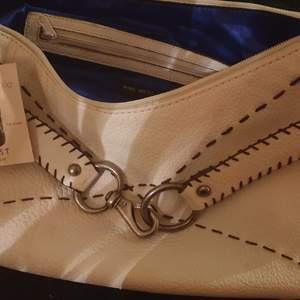 Helt oanvänd vit väska med bruna insydda inslag och fransar. Ingår liten söt matchande väska. Innerfoder mörkblå sidenkänsla