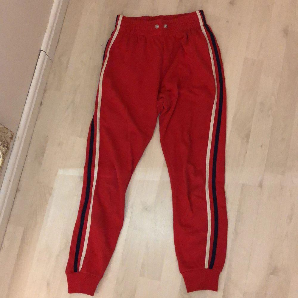 Röda byxor med 2 ränder på sidan från Bik Bok. Använt skicka. Saknar tyvärr snöre i midjan men super fina ändå. Jeans & Byxor.