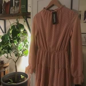 Fin ljusrosa klänning med prickar. Säljer då det inte riktigt är min stil. Lite högre krage. Helt oanvänd med prislappen kvar. Stl 38. Frakt tillkommer