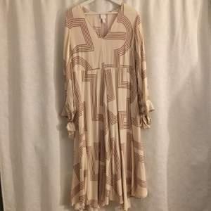 En lång härlig klänning från H&M som användes en gång, kostade 400:-. Frakt tillkommer:) Den funkar som en härlig oversize klänning för mindre storlekar också!