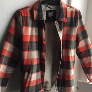 Snygg och mysig fodrad overshirt från Santa Cruz. Passar med tjockare tröja under eller under en väst. Jag har XS och denna sitter lagom. Katt finns i hemmet.