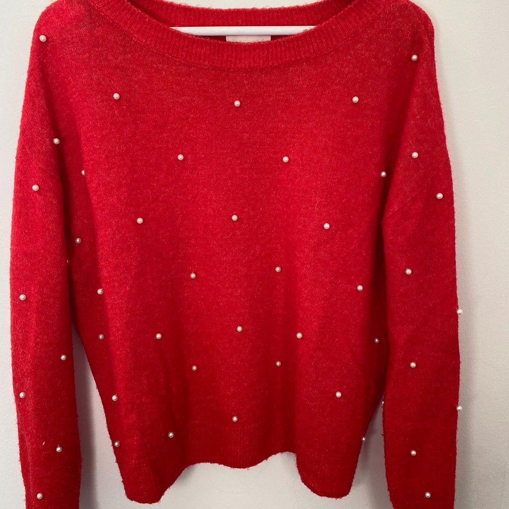 En röd stickad tröja med vita pärlor från H&M. Storlek M men passar både S och L beroende på hur man vill att den ska sitta på. Väldigt fint skick då jag bara använt den ca 3-4 gånger. Köparen står för frakten❤️. Tröjor & Koftor.