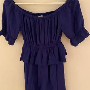 En jättefin blå klänning. Använd en gång så i ett bra skick. Fina volanger och formar kroppen fint.