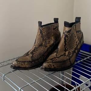 Supersnygga boots i ormakinnsmönster. Materialet är läder och strl 39. En aning slitna, men snyggt.