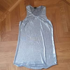 Silvrigt linne med brottarrygg. Funkar som miniklänning om man är en s eller xs.