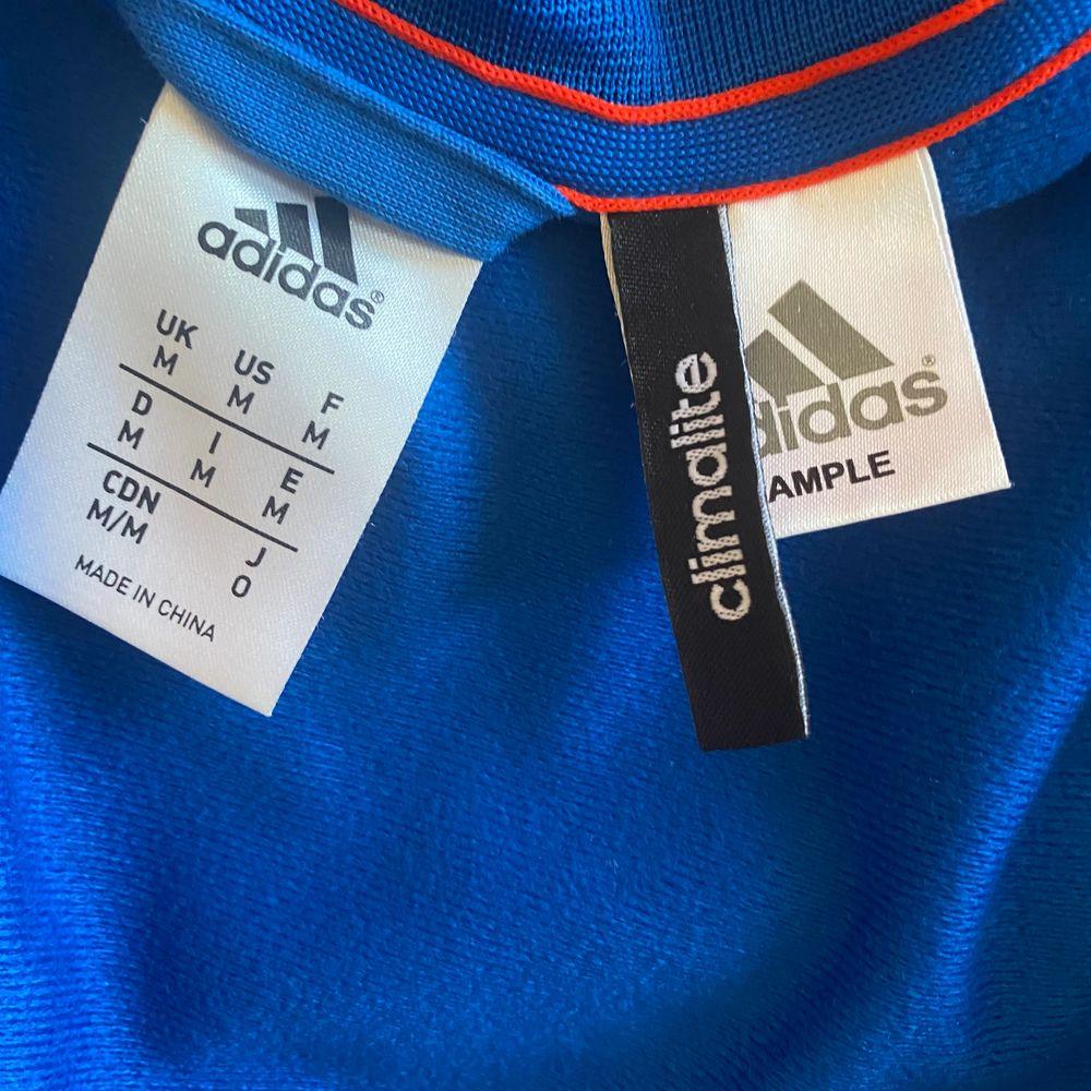 Adidas trackjacket. Köpt på second hand i californien för två år sedan. Ovanlig modell med drapering i vitt fram och oranga ränder längs sidorna . Huvtröjor & Träningströjor.