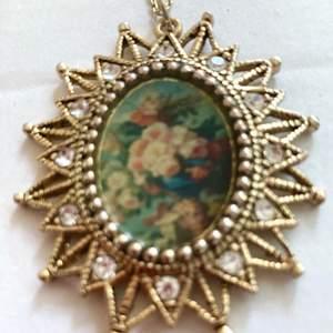 Hänge med blommotiv , gulmetall , nickelfri . Kristaller o stenar . Höjd 2.7cm bredd 2 cm .