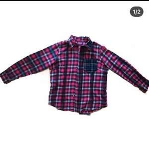 En skjorta som är omgjord med sprayfärg i olika färger samt tyg från andra skjortor! det står att storleken är L men jag tycker att den är liten i storleken, jag skulle säga att den passar mer M! Plaggets längd är ca 66 cm.