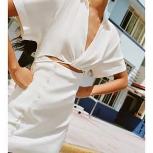Oanvänd vit klänning med vit out. Storlek S.