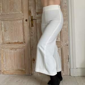 Vita siden kostymbyxor med dragkedja i sidan. Sitter perfekt i midjan. Modellen är 172 cm och de funkar bra i benen.