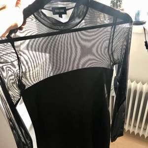 Svart klänning med överdel i mesh-material och lite polokrage. Stretchigt material. Köpt på bubbleroom. Knälängd. Använd två gånger, så i nyskick!