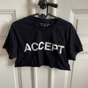 """En svart t-shirt, med texten """"ACCEPT"""",  som jag själv klippt till en magtröja. Går under brösten. Strl S"""
