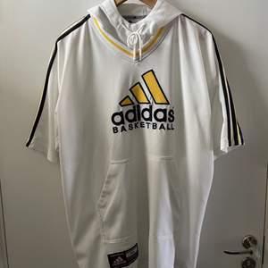 En Adidas Oversize T-shirt tröja med luva köpt second hand i bra skick.