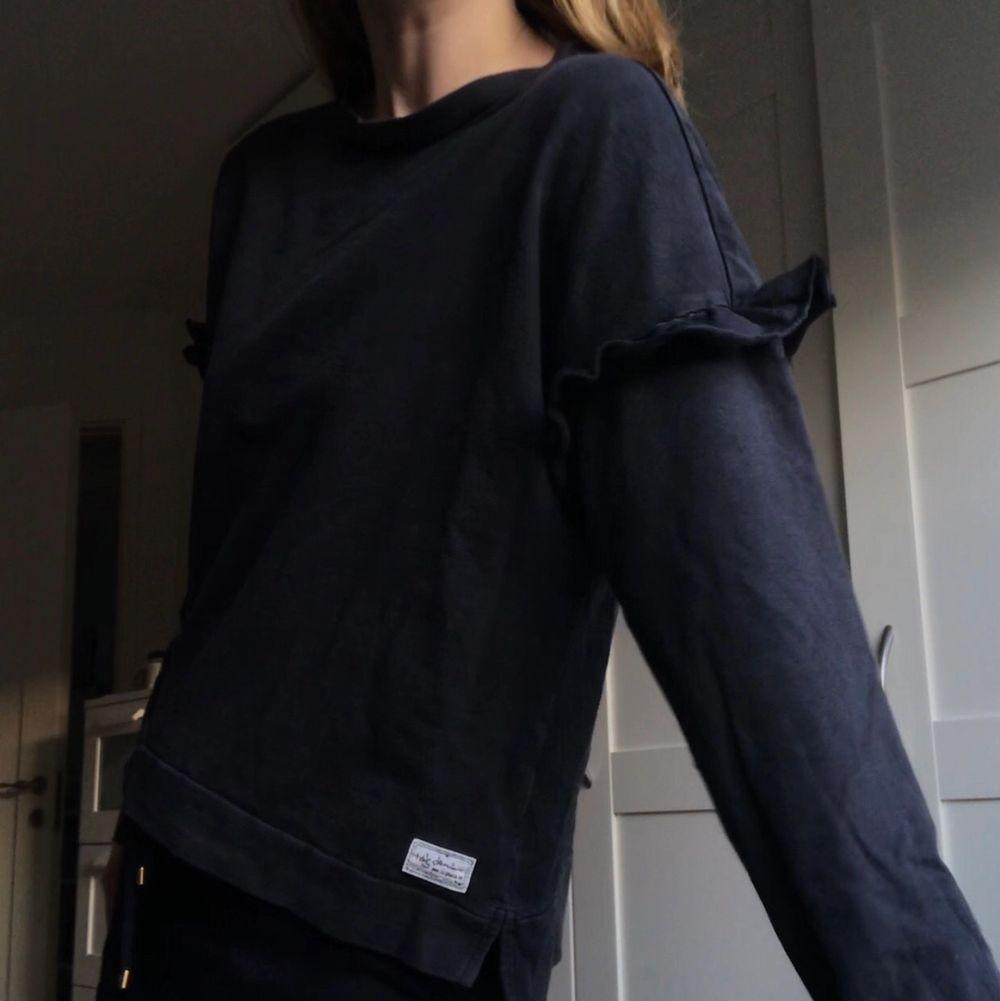 Svart, simpel tröja med volang från I dig denim! Sparsamt använd. Huvtröjor & Träningströjor.