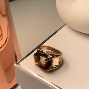 En guldig ring med bruna ditaljer i storlek M!💍☺️💍 buda! (Kan skicka men köparen står för frakt;)