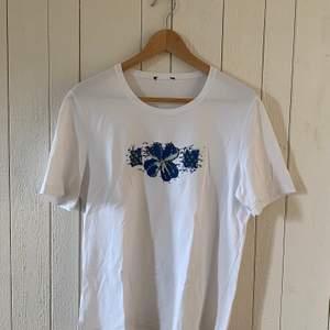 Vit t-shirt med blåa blommor i paljetter. Passar som storlek M. Märke är okänt. Mycket bra skick.