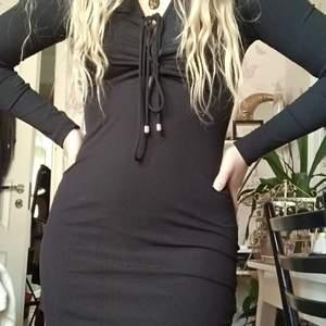 Tight svart klänning med långa snören som snöras över bröstet, snörena är justerbara. Långa armar och klänningens längd går till mitten av mina lår, jag är 161 cm lång. Mjukt tyg som inte skaver. Säljer p.g.a att jag aldrig använder den. Pris kan alltid diskuteras!