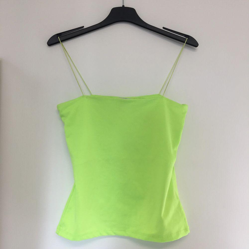 Neongrön topp med smala spagettiband. Mer lysgrön i verkligheten än på bilden. Storlek XS men passar S också.. Toppar.