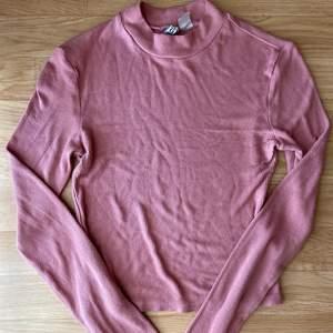 ribbad rosa tröja, lite längre upp i halsen & lite kort