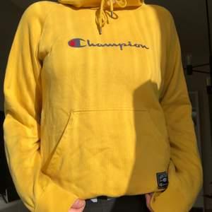 Gul champion hoodie i storlek S, passar även M.  Ett litet hål precis vid snörningen, syns på bild 3.