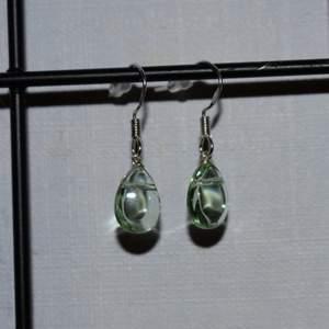 Handgjorda örhängen med gröna pärlor i form av droppar. De görs vid beställning och är därmed helt oanvända. Krokarna är gjord av äkta silver. Kolla gärna in min profil för fler handgjorda örhängen :))