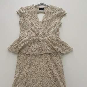 Oanvänd vit/beige klänning som är ungefär knälångd. Den har en liten öppning i ryggen.