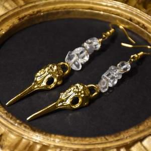 Örhängen med guldiga fågelskallar och äkta bergskristall. Krokarna är nickelfria.