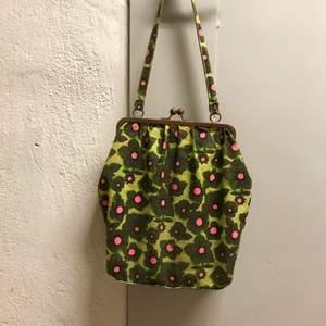 Helt underbar väska i grönt och rosa med blommigt mönster. Knäppe som stänger väskan och ett fack inuti. Kan mötas i Stockholm eller skicka mot fraktkostnad! ✨🌸✨
