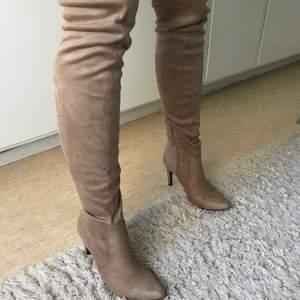 Beige, brun boots i mocka liknande material. (Knähöga stövlar med klack). Klack höjd: ~8cm. Storlek 36 men jag funkar för mig som har 37
