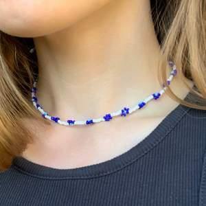 Hemgjort pärlhalsband med blommor. Halsbandet är 38 cm och av plasttråd med hasp som kan knäppas i nacken. Jag kan på beställning göra liknande med andra färger och pärlor eller annan design (se bild tre för utbud av pärlor).