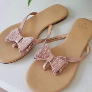 Sandaler med glittriga rosetter från Oasis. Söta flip flops till sommaren! Bara använda 2 gånger så i fint skick!
