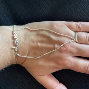 Så fett o coolt handsmycke. Silverfärgad står LOVE på. Ringen är ställbar. Just nu 17mm. Reglerbar längd runt handled. Buda gärna. Frakt 15kr