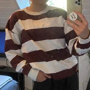 En randig sweatshirt av vit och vinröd. Något oversized då det är S i herrstorlek men sitter hur snyggt som helst.