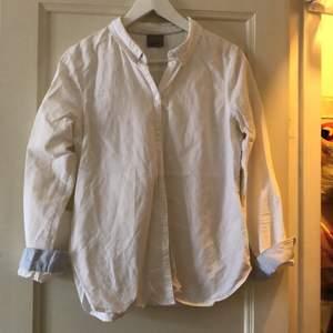 Vit skjorta, måttligt använd. Inga fläckar. Inga defekter. Ljusblå detaljer i hals och krage.