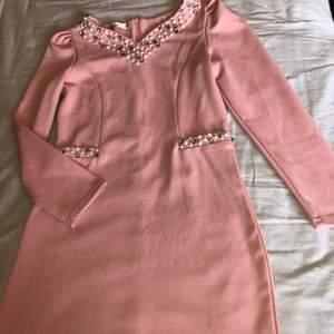 Sjukt fin rosa klänning ganska kort och formar sig efter din kropp. Paljetter vid halsen och fickorna men fickorna  är ej äkta. St:S Säljs pga kommer inte till användning, fläcken på klänningen är inte på utan den kommer från min kamera (köparen står för frakten):)