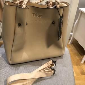 Dior inspirerad väska som är krämvit/beige oanvänd. Fint skick men har några små repor såg jag när jag synade väskan men inget som syns knappt.