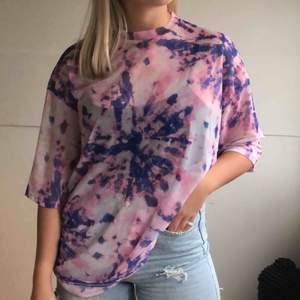 Rosa/lila tie-dye mesh t-shirt från junkyardcom  Använt ca 2-4 gånger, ny skick Modell av en lång oversized t-shirt i rosa mesh material med lila och lite svarta tie-dye detaljer  Kommer inte ihåg ny pris,