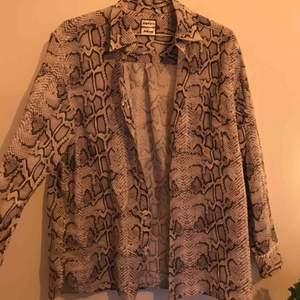 Ormmönstrad skjorta från Eytys kollektion med H&M. Använd max 3 gånger och i väldigt bra skick. Den är ganska oversized så kan passa olika storlekar. Skriv för mer bilder/info. Kan mötas upp i Gbg/köparen står för frakt❤️