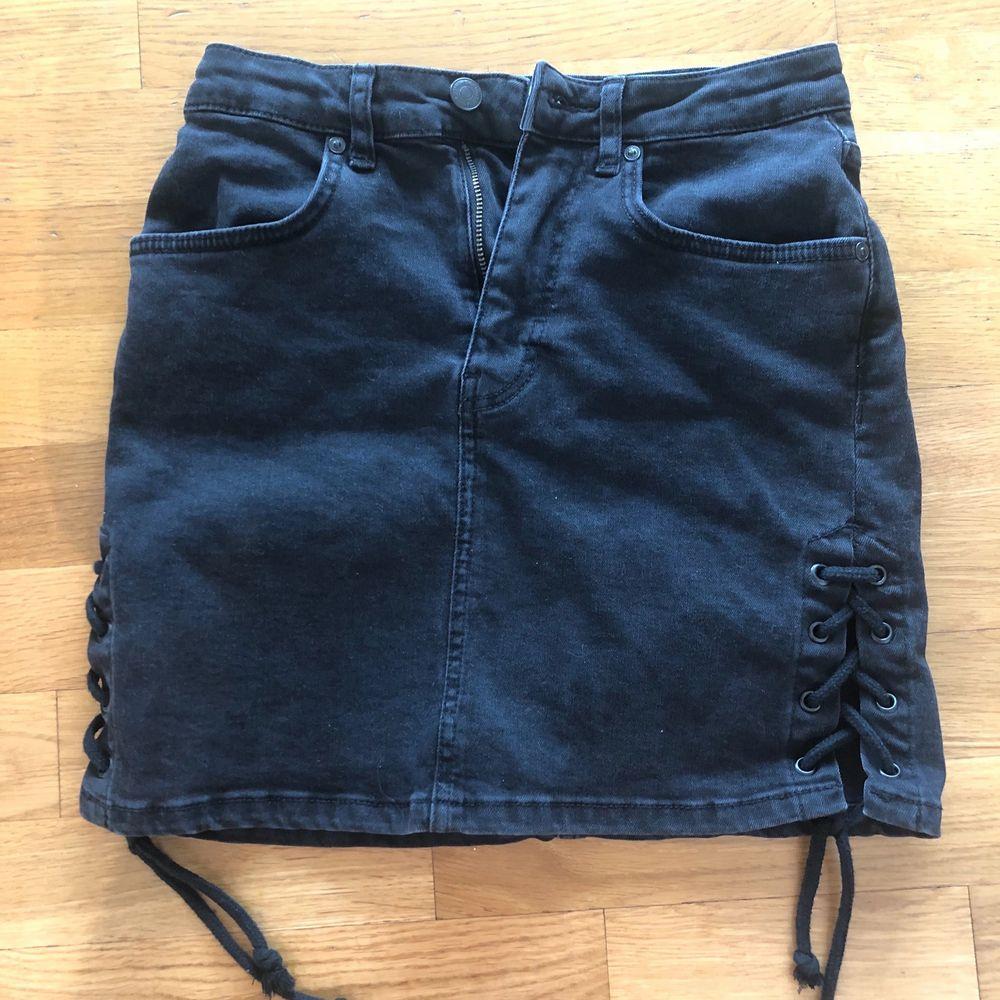 Svart jeanskjol med snörningar i sidorna från Gina Tricot, storlek 34. Använd en gång.. Kjolar.