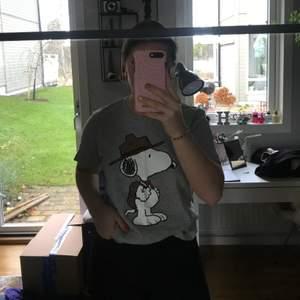 Grå T-shirt med snobben tryck på. Väldig bra skick och inga täcken på användning finns. Köparen står för frakt.