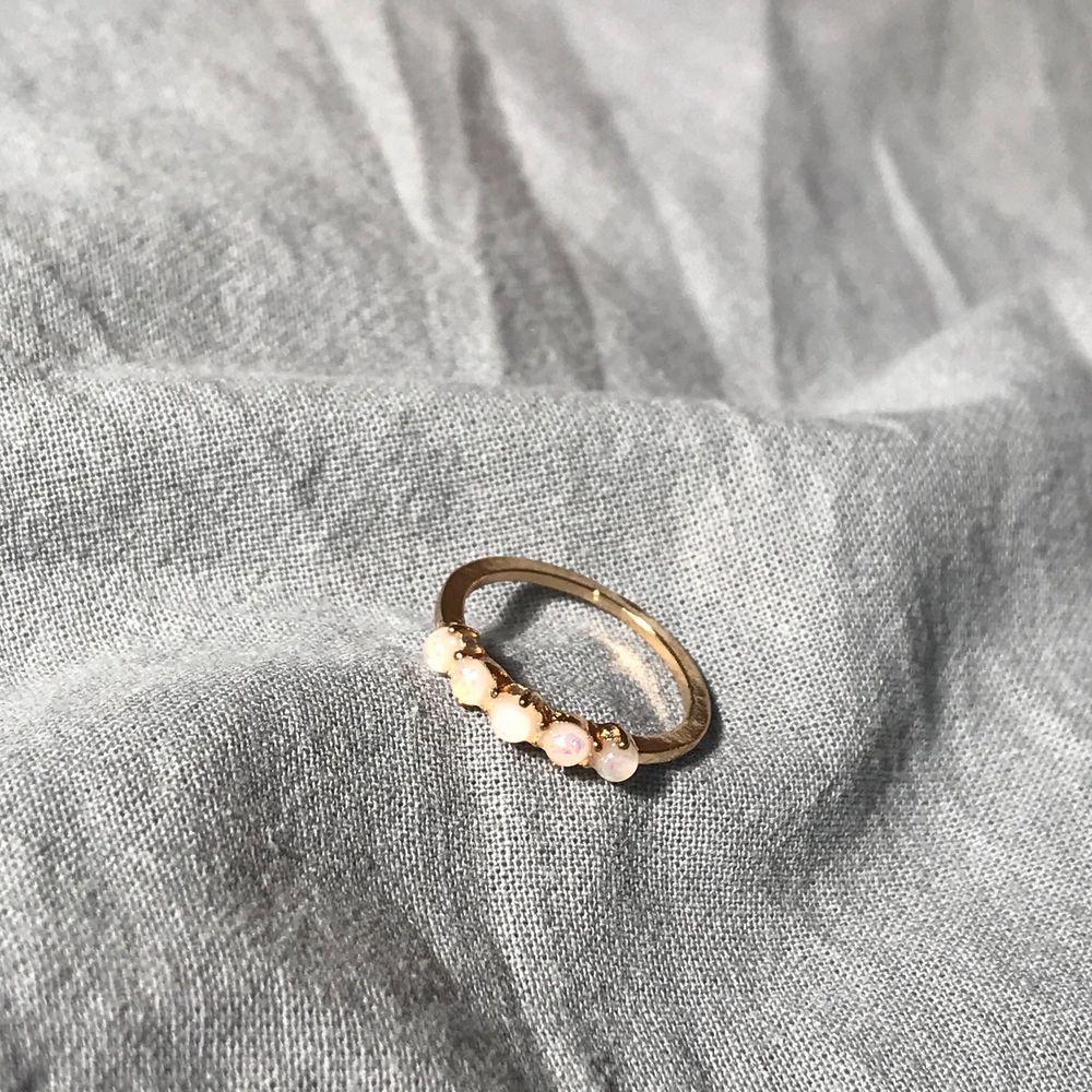 Guldig ring med 5 små stenar på rad. Köparen betalar frakt❣️. Accessoarer.