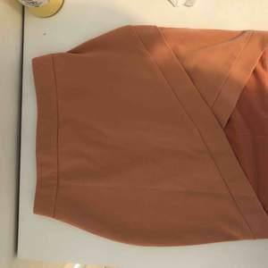 Pennkjol i en ljusrosa/aprikos färg
