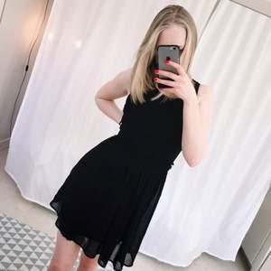 Svart klänning med snygga detaljer framtill. Jag är 172 cm och på mig är den lite ovanför knäna. Man kan ha skärp i midjan och dra upp den lite om den känns för lång!  Kan mötas i Stockholm eller frakt 49kr