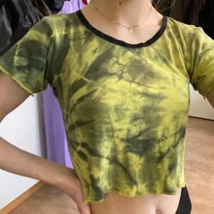 En grön/gul spräcklig t-short som är lite croppad i modellen!