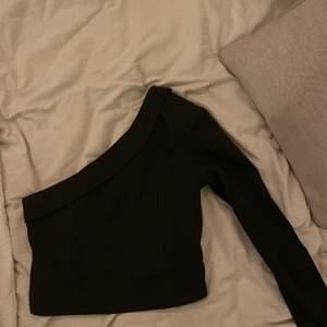 En svart tröja i kostymmaterial med en arm som passar till både fest och till vardags.  Kort men inte som en magtröja riktigt. Knappt använd på grund av för liten i storleken så som ny i skicket! Köparen står för frakt.