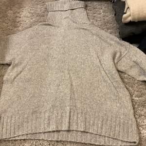 Grå stickad tröja som är lite oversized