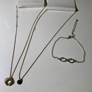 2 oanvända halsband, ett med ringar och ett med en svart sten. Silver armband storlek M-L i storlek med evighetstecknet, alla för 20