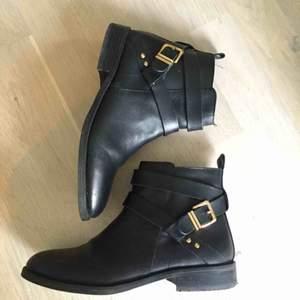 Snygga svarta skinnskor med gulddetaljer. inköpa på din sko. Jättefint skick. Används enstaka gånger. Nypris: 899:-