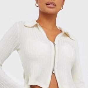 Säljer denna populära vita topp med dragkedja från Nelly. Dragkedjan kan dras både upp och ned på båda hållen. Storlek Xs. 180kr+frakt
